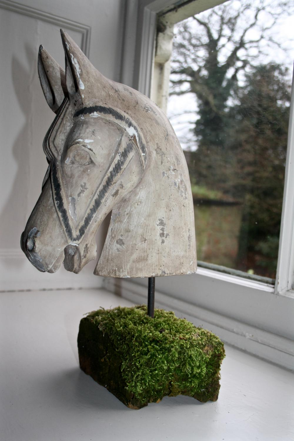 Wooden horse's head mounted on old brick