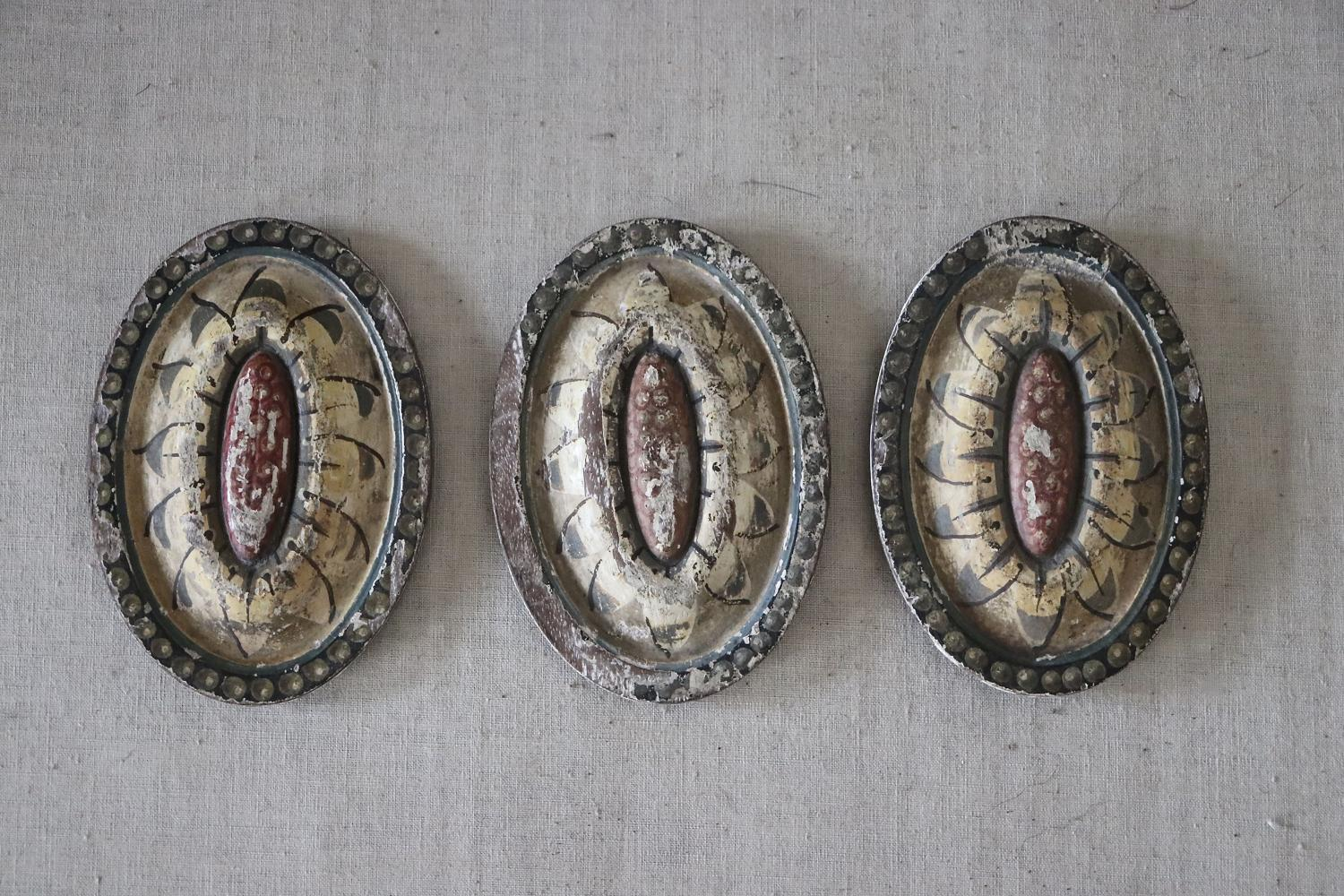 Three painted wooden plaques
