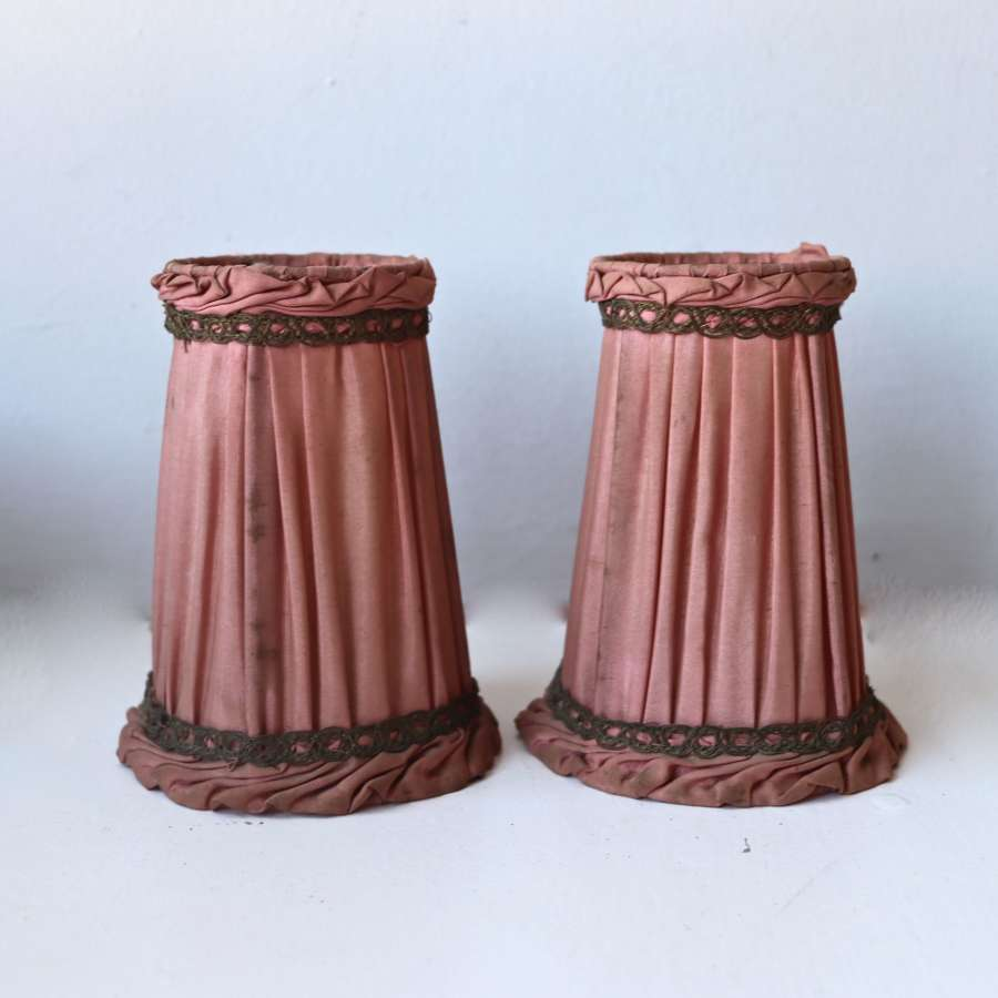 Pair of small salmon coloured pleated and metallic braided lampshades