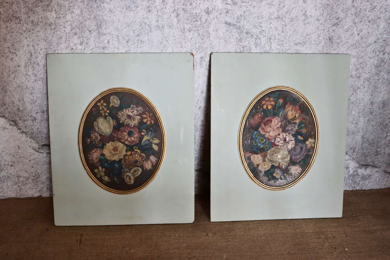 Pair of painted wooden panels with oval floral paintings