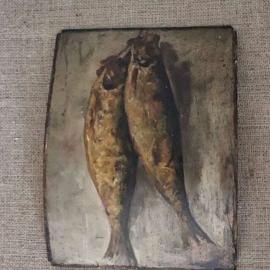Still life of hung fish on bowed veneered wood